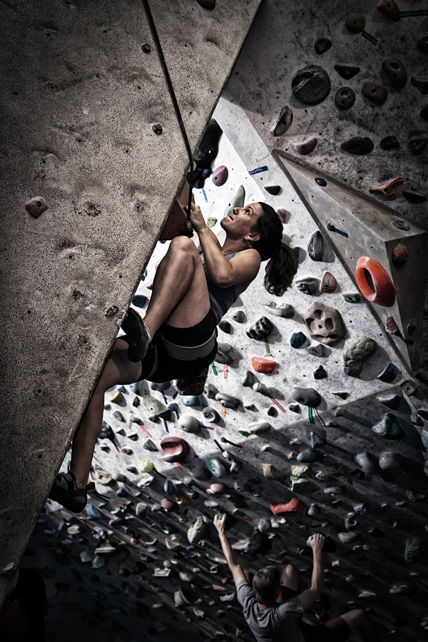 Elana climbs a climbing wall in a climbing gym.