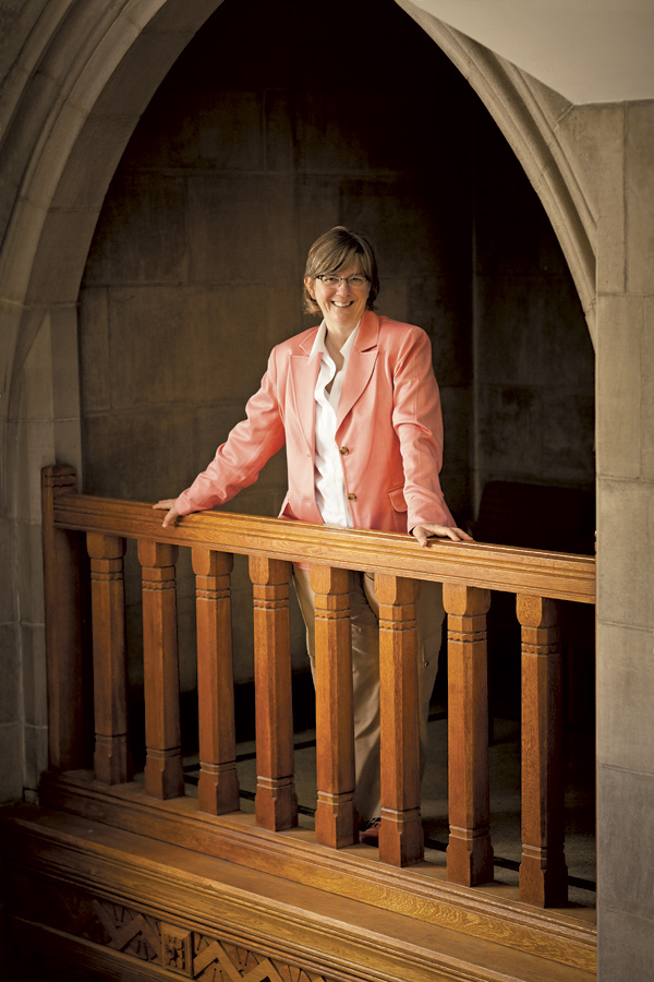 A member of the Emmanuel College faculty stands in an archway.