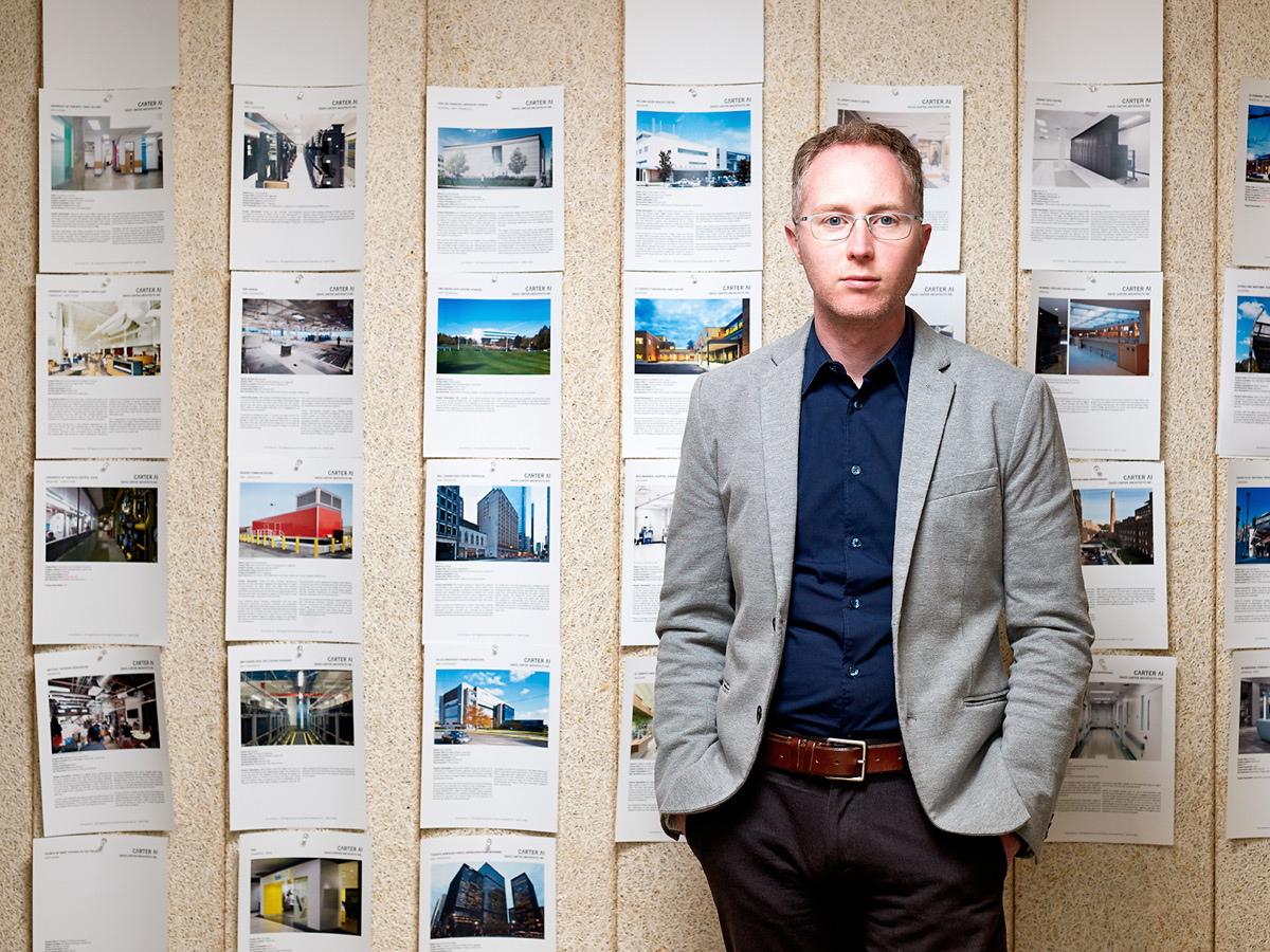 Alan stands in front of wall of paperwork at David Carter Architects