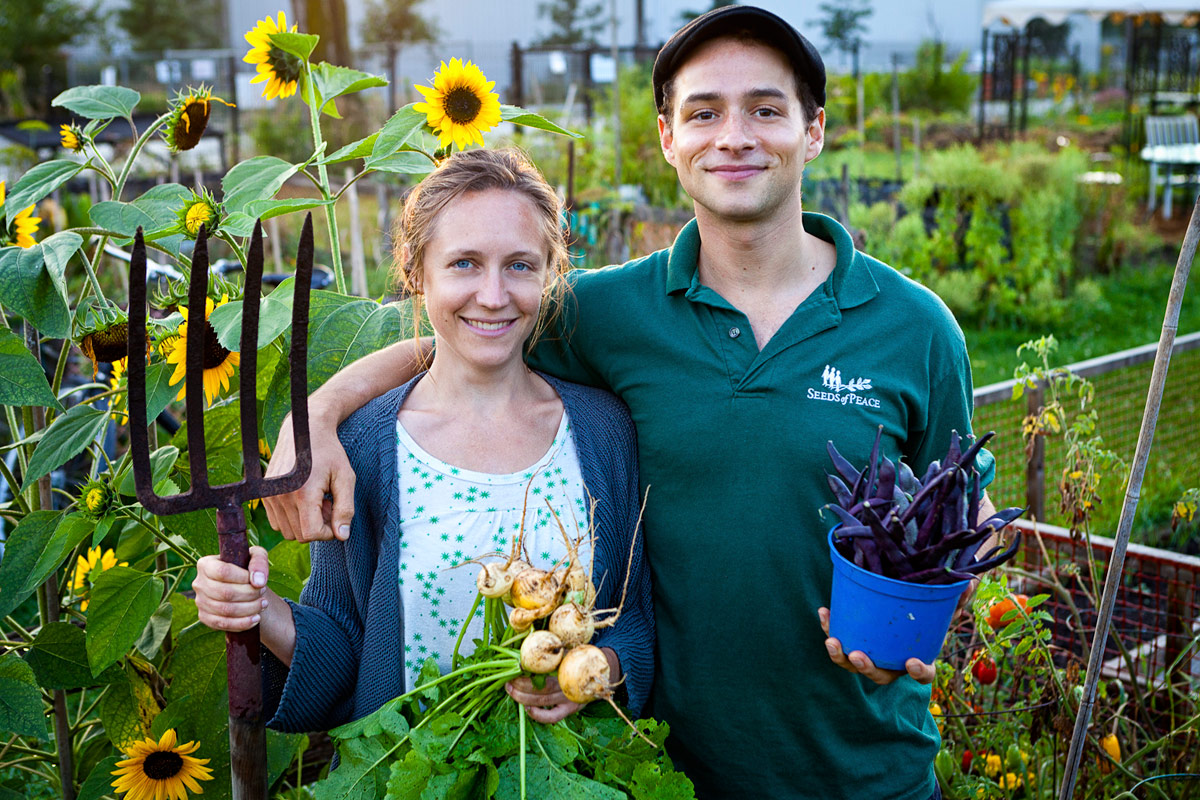 Julie and Adam in their allotment garden holding produce.