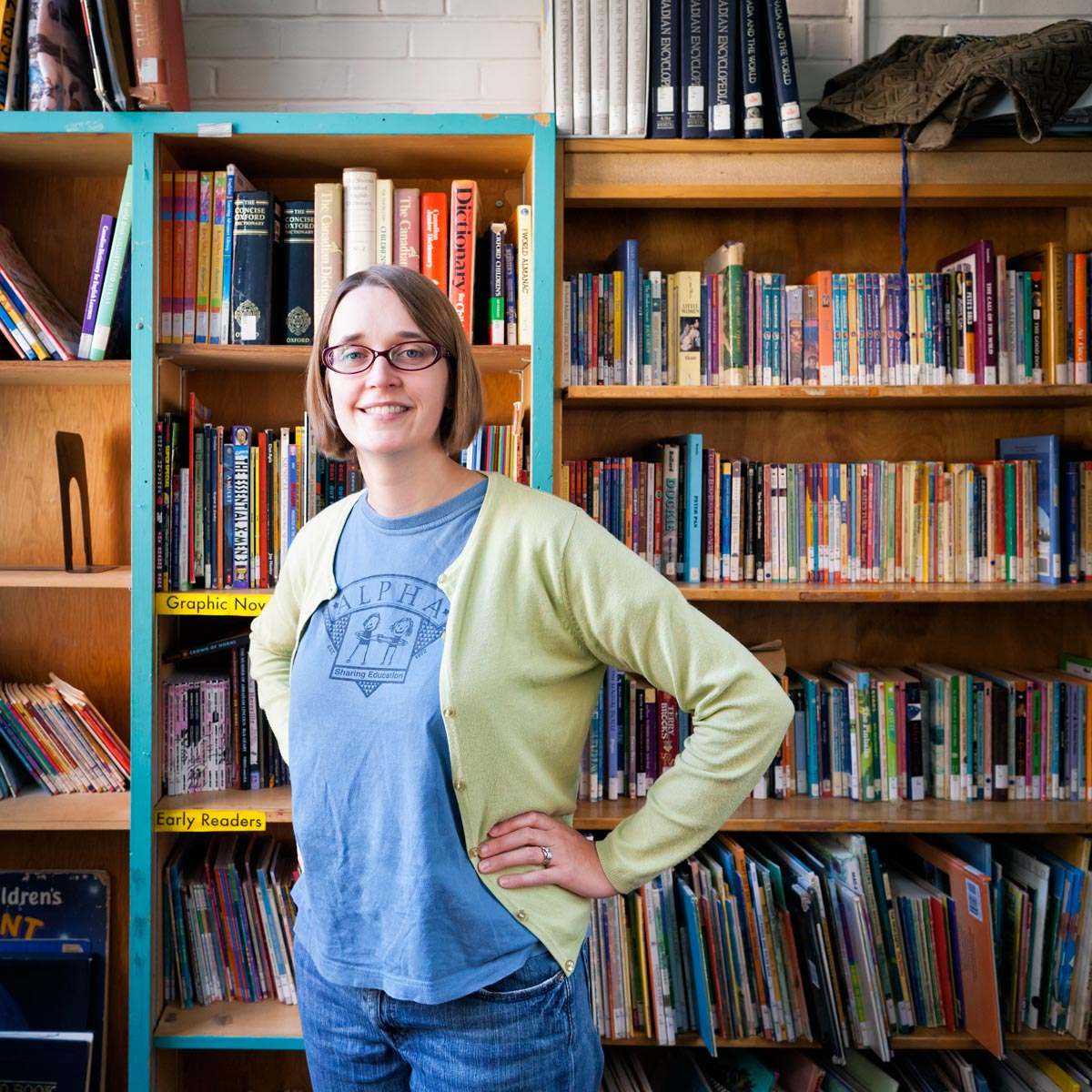 Maggie Marelli stands in front of book shelves at Alpha Alternative School