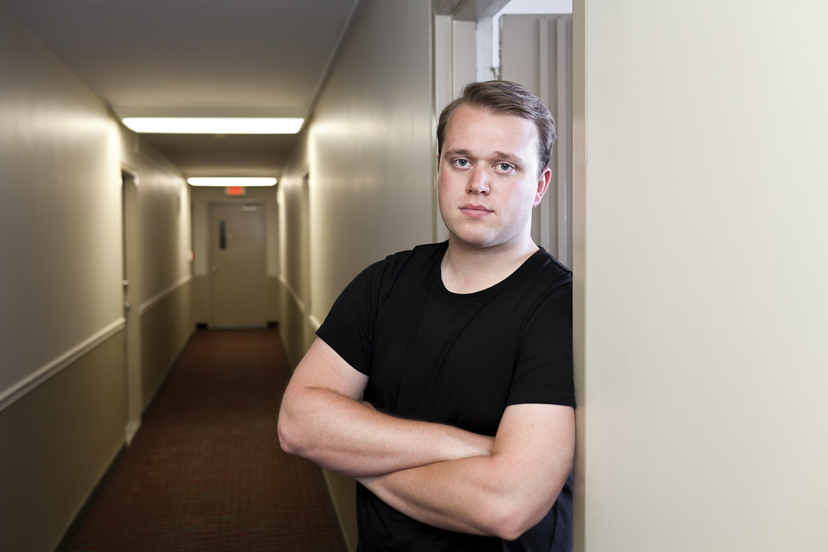 Author Jack Urwin in a hallway in an apartment building.