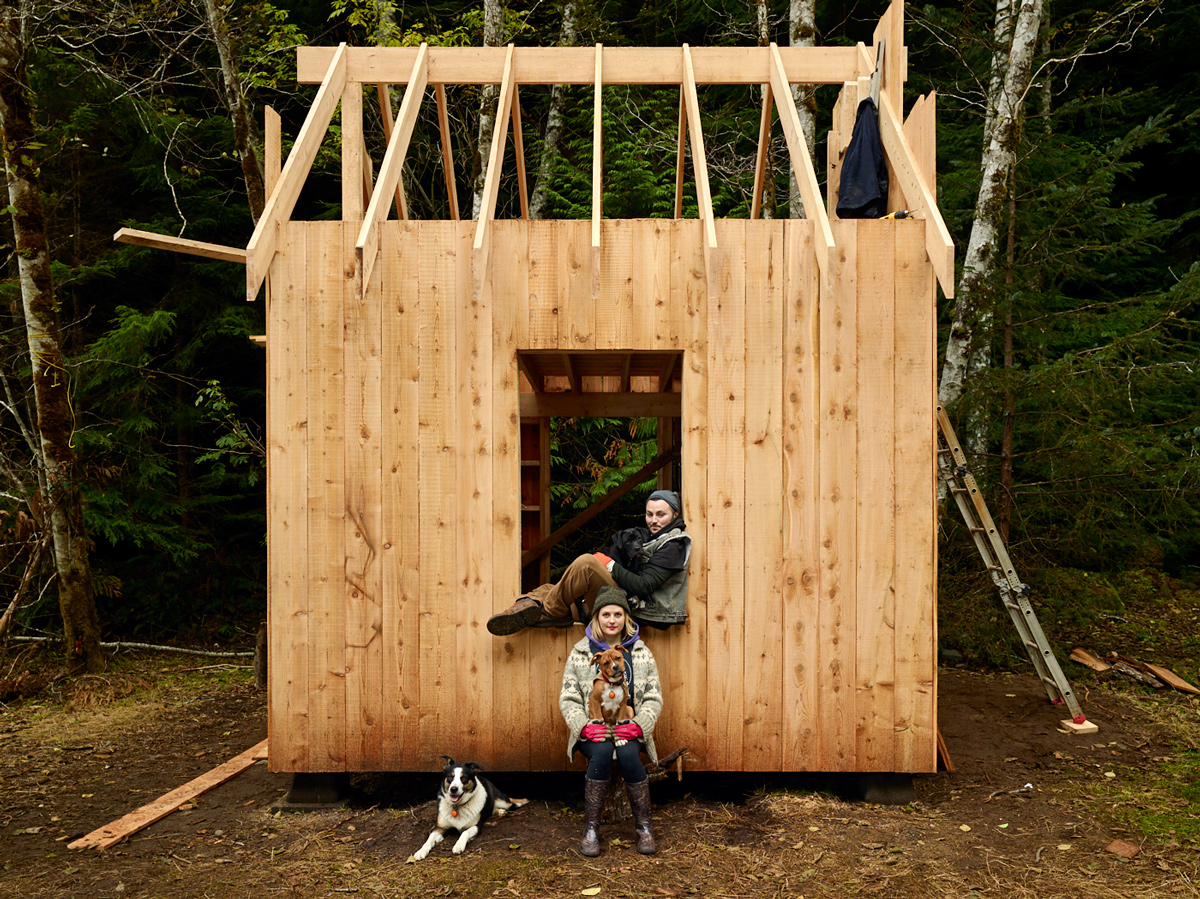 andi grace rose and logan hope rose with their dogs dolly, bousha, and clover. Photographed with the first timber frame structure at their new home, fiddlehead farm on Malcolm Island. Sointula, British Columbia.