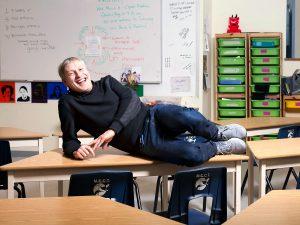 Triangle Program teacher Jeffrey White lies on a desk in a classroom