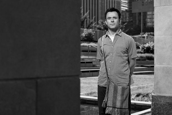 Portrait of Alex Pereklita standing in the Peace Garden at Nathan Phillips Square in Toronto.