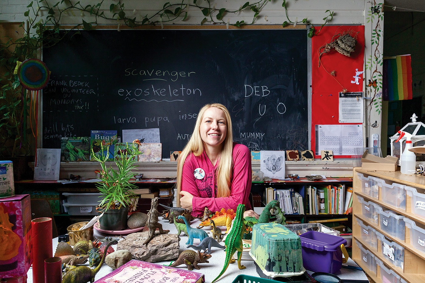 A woman in a pink pullover sits at a table in front of a blackboard in a classroom surrounded by books and toy dinosaurs