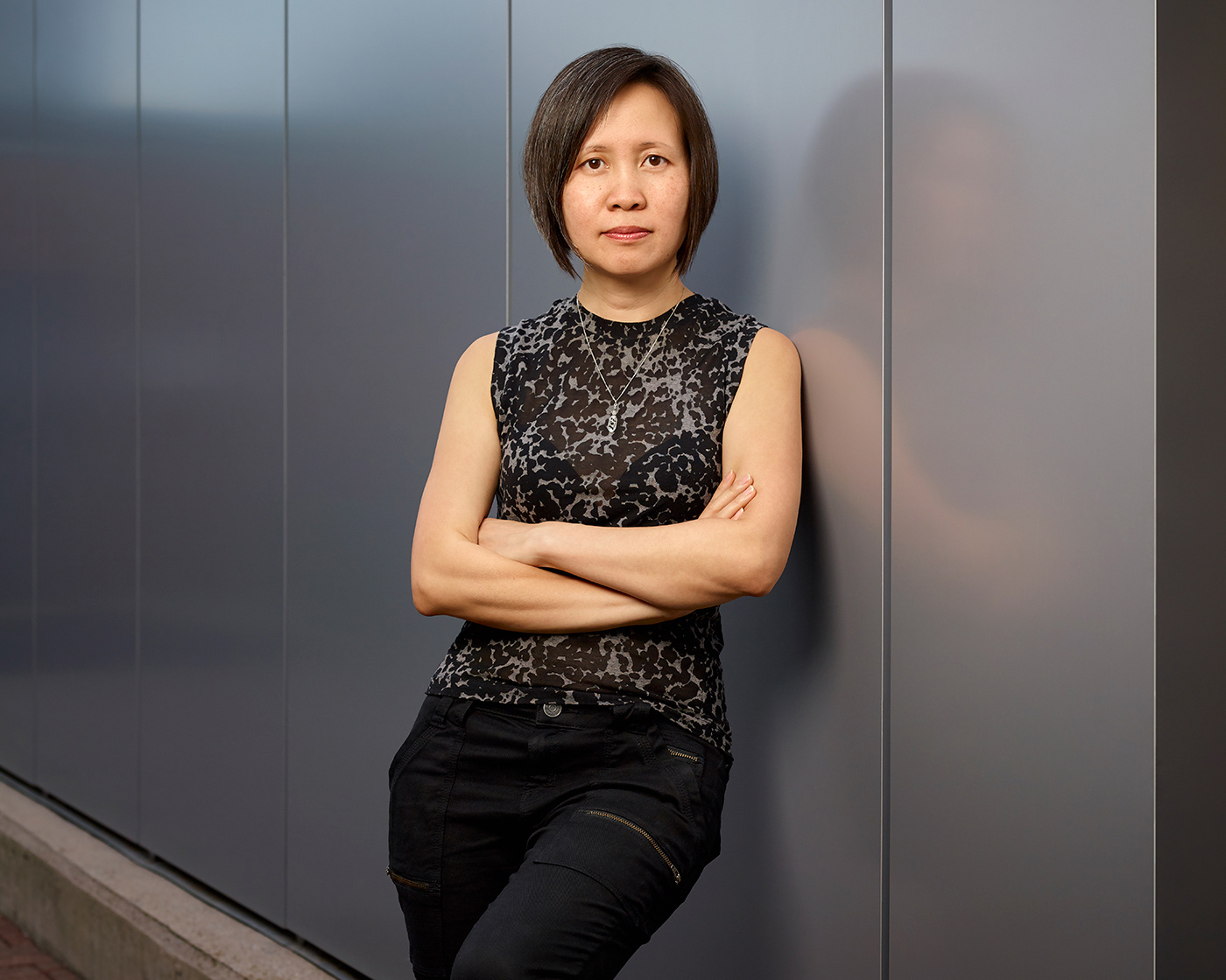 Image of cinematographer Iris Ng leaning against a wall with her arms folded.