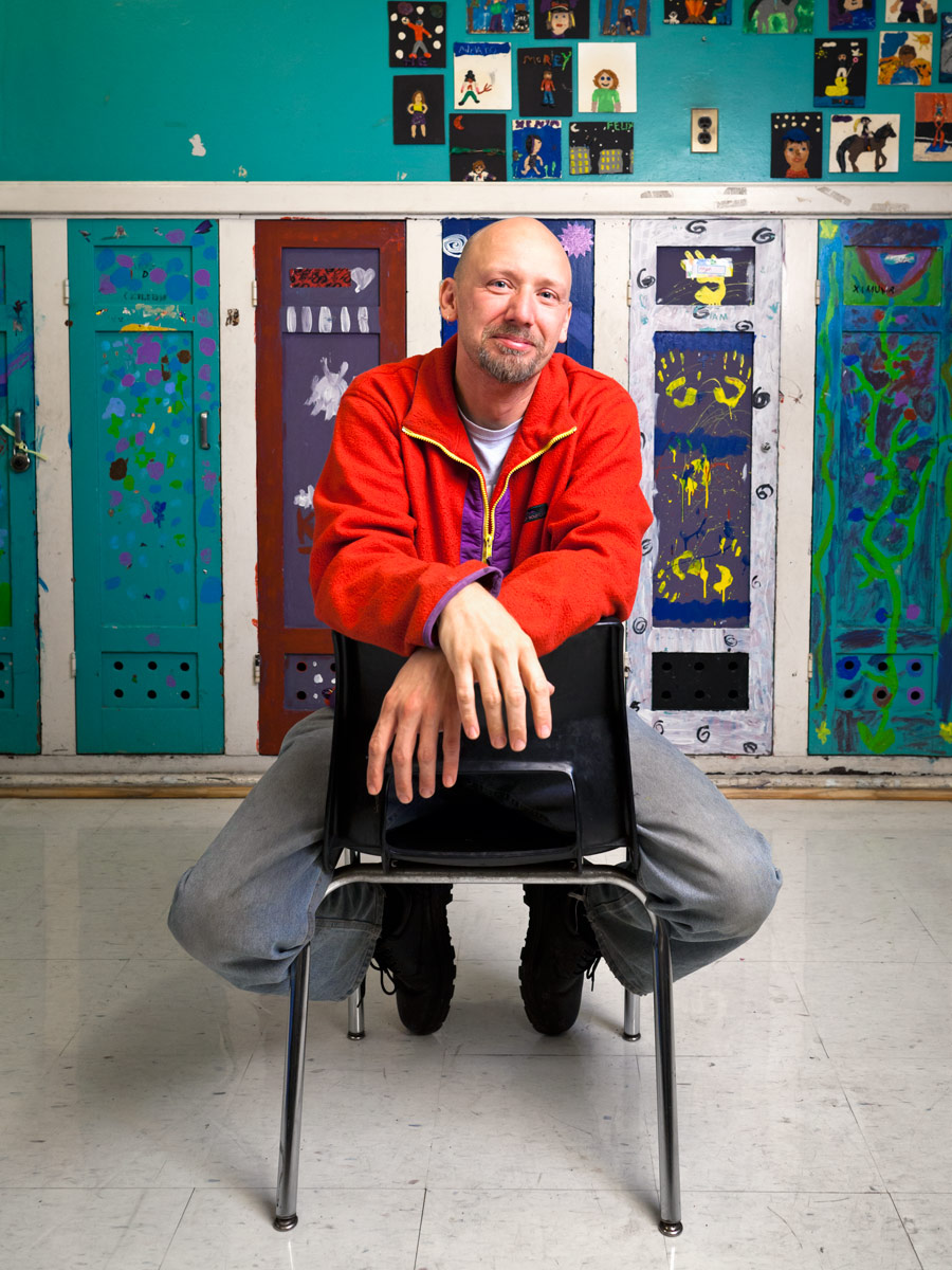 Morgan Jones Phillips sits on a chair in a classroom at Alpha Alternative School in front of a row of colourful painted lockers