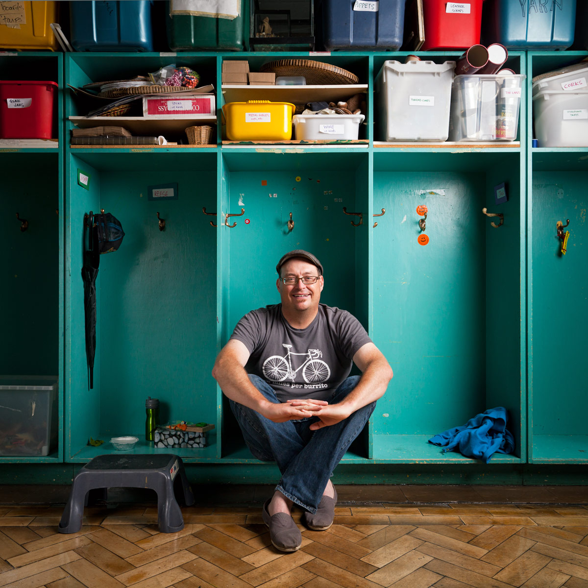 Stefan Lynch Strassfeld sits in a cubby hole in a classroom at Alpha Alternative School