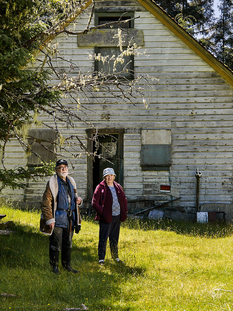 "James ""Jimmy"" Michael Poulton and Nancy Olga Poulton/Lanqvist stand in front of the house they used to live with their mother ""Toots"" (Johanna Laura Poulton) over 50 years ago. Built in 1904 on this site on Rauhala heritage farm, it is one of the last buildings still standing built by the Kalavan Kanssa Finnish settlers. Nancy's son Roger Léo Lanqvist hopes to restore the building and turn it into a museum. Sointula, British Columbia."