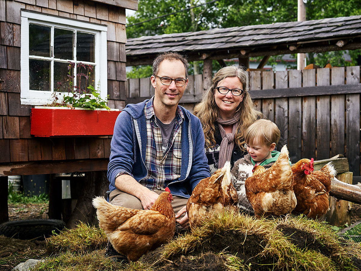 Artists Tyler Brett and Kerri Reid, co-directors of the Sointula Art Shed, with their son Teddy and their chickens, all named Darlene, in front of the chicken coop Tyler built with help from Teddy. Tyler also works as a paramedic, and was recently hired as Sointula's first Community Paramedic, and Kerri works from home for Living Oceans Society. Sointula, British Columbia.