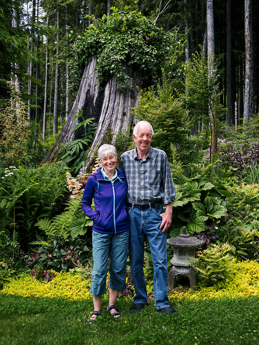 Shirley and Vern Sampson stand in front of an old growth cedar stump in their garden in Rough Bay, Sointula, British Columbia.