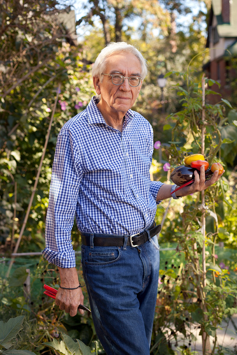John Sharkey holds vegetables and garden shears in his garden in the Bain Co-op.