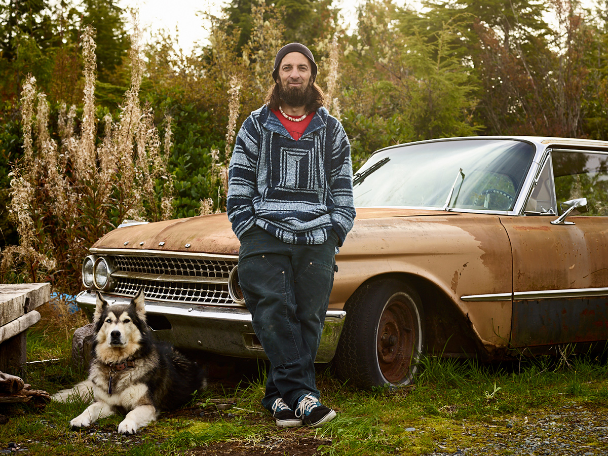 Grant McCormick with his ten-year old dog Luna and the 1961 Ford Galaxy he's planning to restore one day. Sointula, British Columbia.