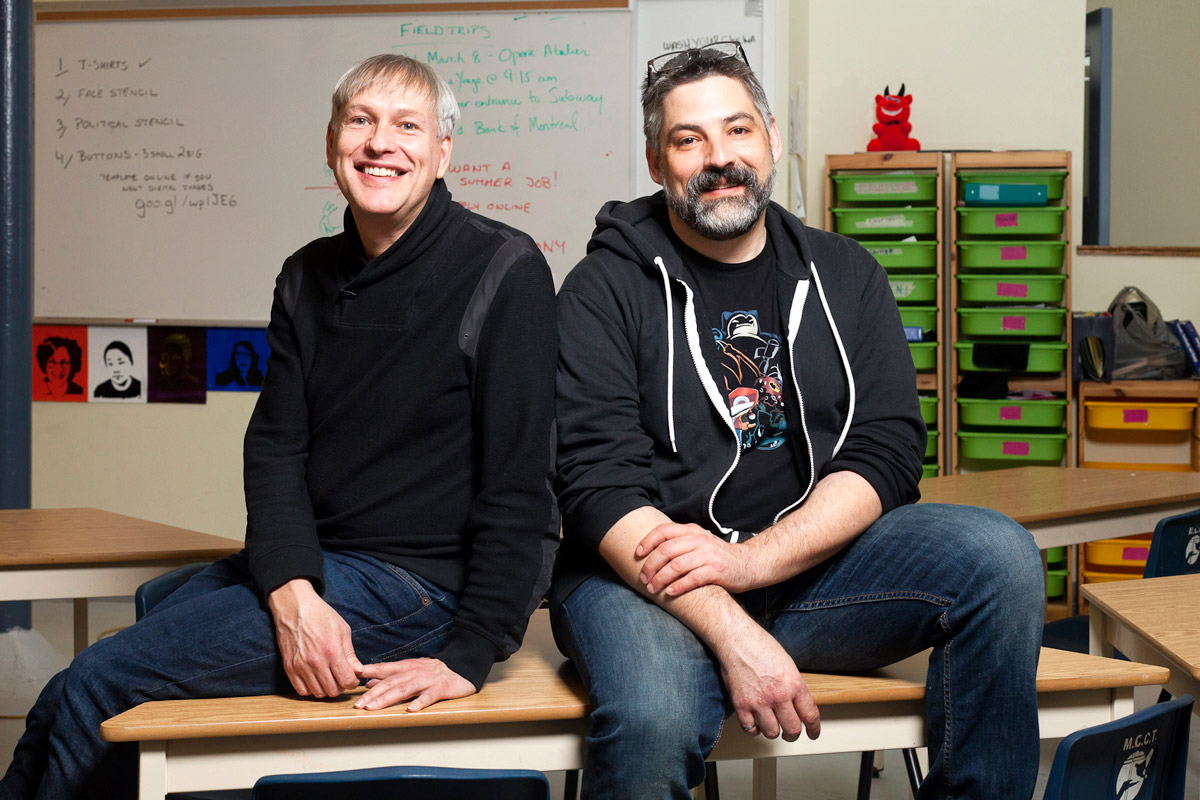 Triangle Program teachers Jeffrey White and Anthony Grandy sitting on a table in a classroom