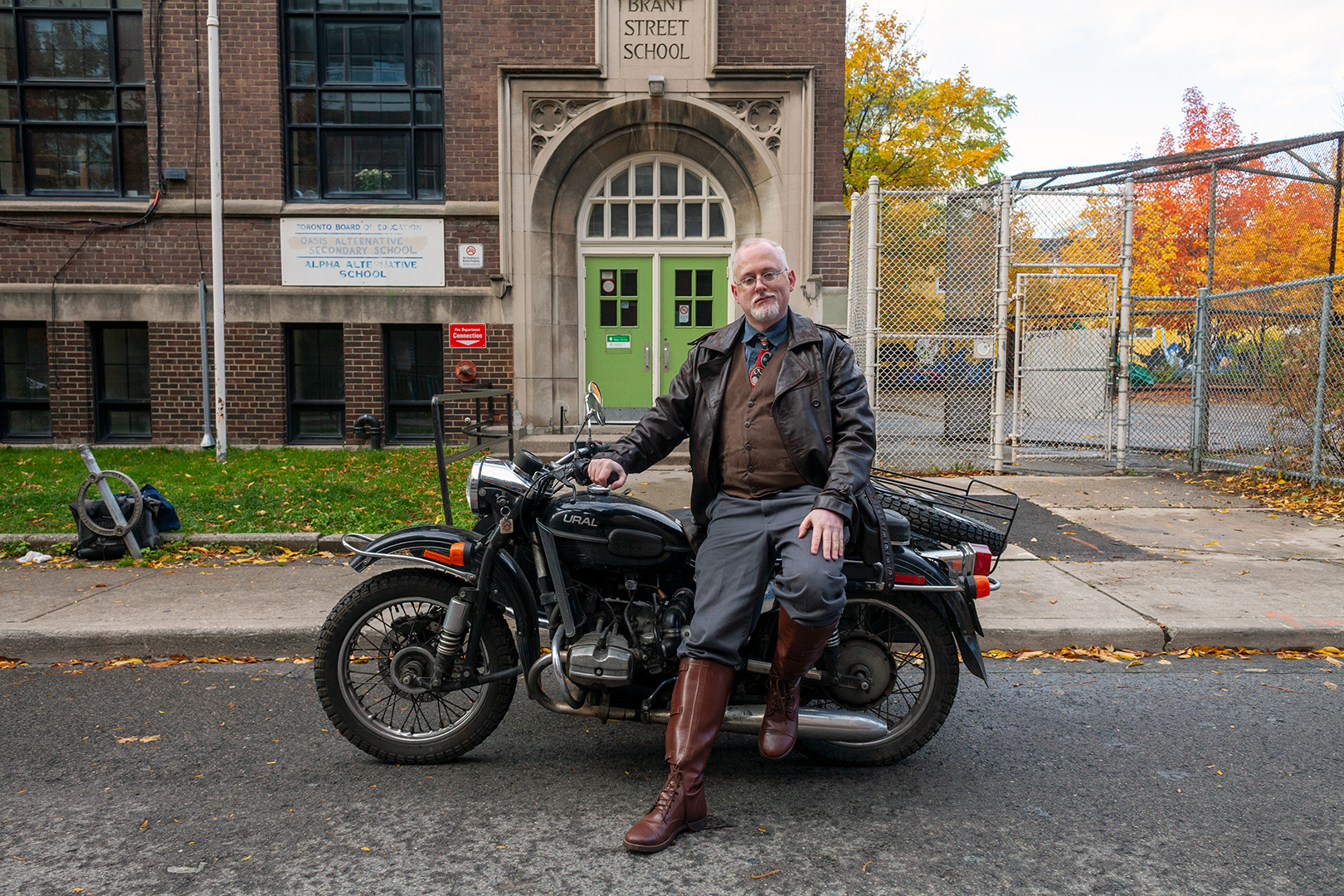 Jamie Leonard sits on a Ural motorcycle in front of Alpha Alternative School