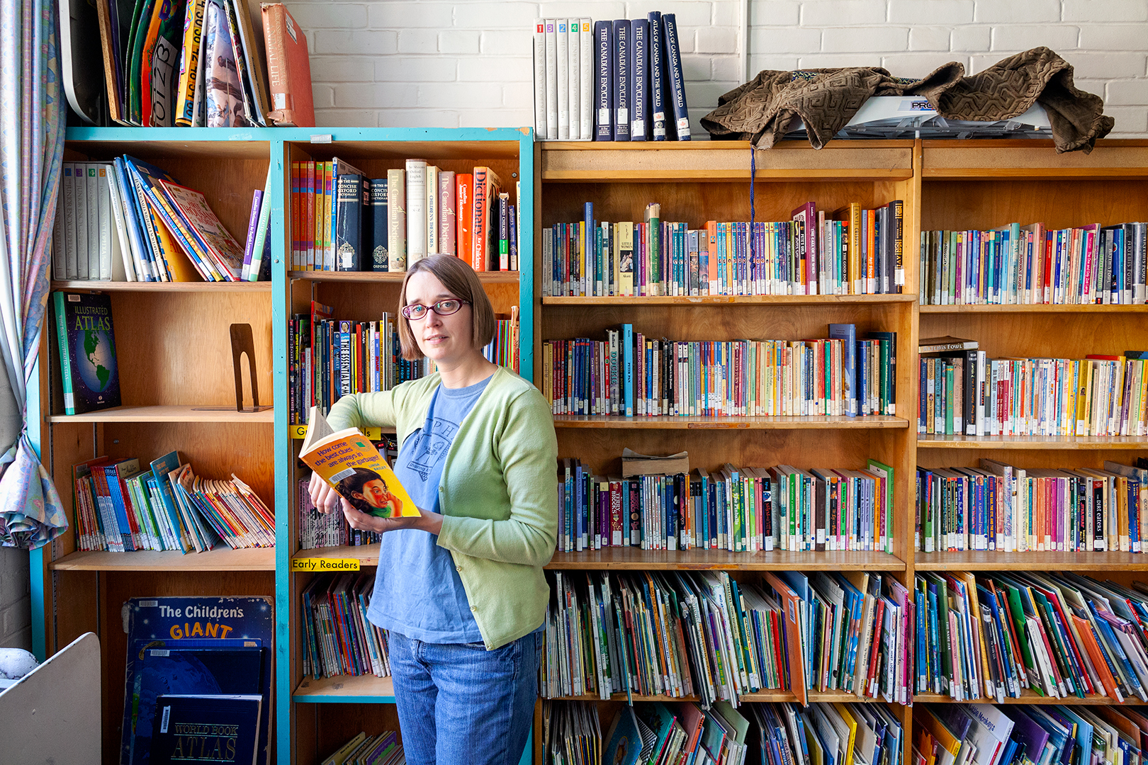 Maggie Marrelli stands with a book in hand in the library at Alpha Alternative School