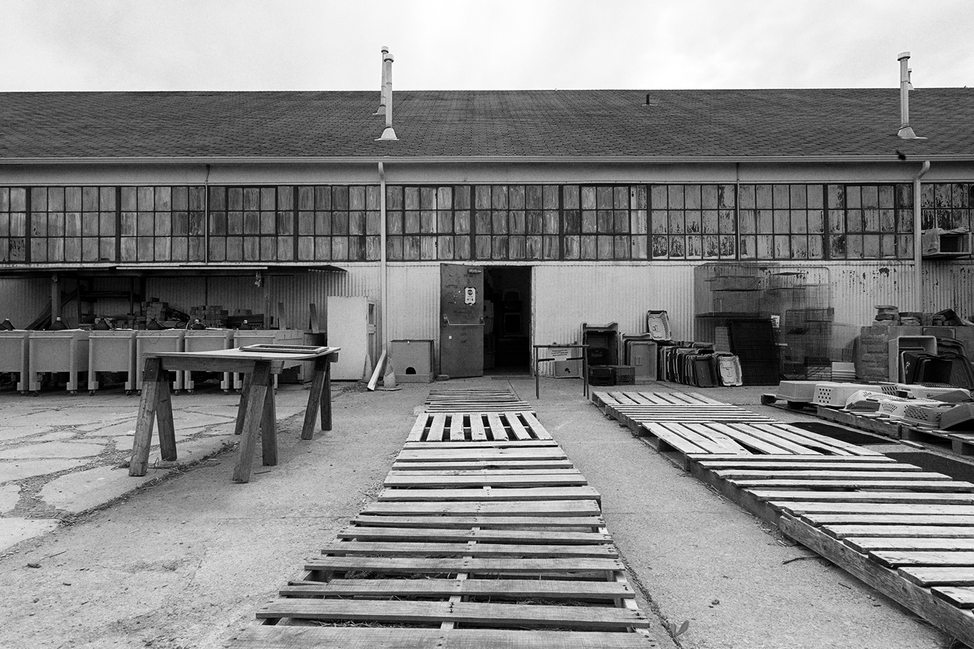 A large yard in front of low building, there are many wooden pallets in the yard.